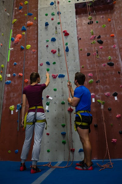 Low angle view of male trainer guiding woman in climbing wall