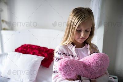 Girl holding heart shape pillow on bed
