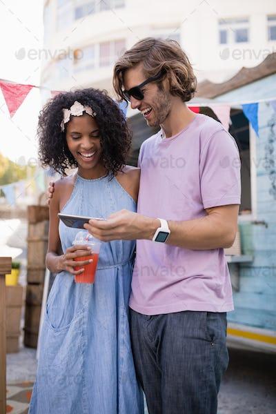 Happy couple using mobile phone