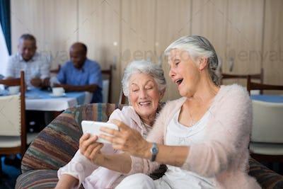 Senior friends taking selfie through smart phone