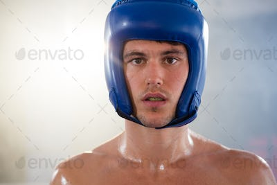 Close-up portrait of young male boxer wearing blue headgear