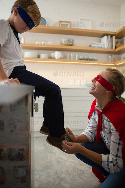 Mother with son in superhero costume tying his shoelaces
