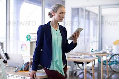 Female executive using digital tablet at her desk