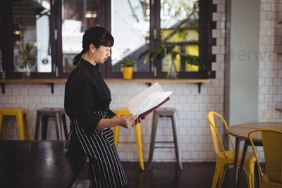 Side view of young waitress reading menu while leaning on table