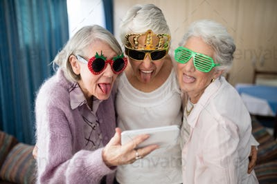 Senior women wearing novelty glasses making face while taking selfie