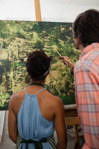Man assisting woman in painting