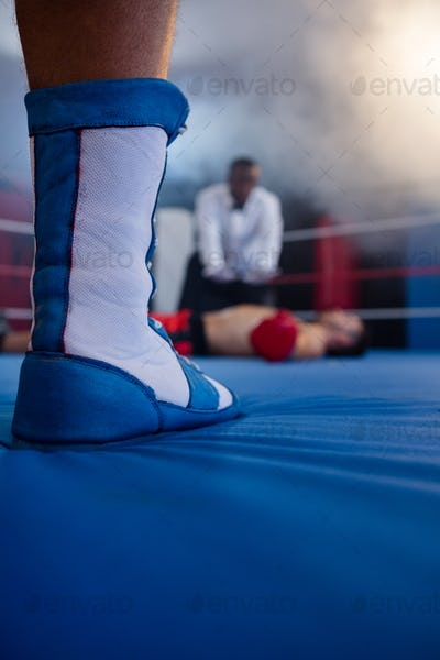 Low section of boxer standing against referee by athlete