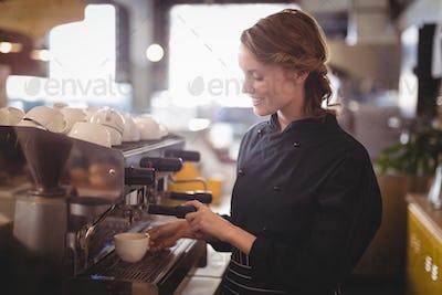 Smiling young waitress using espresso maker