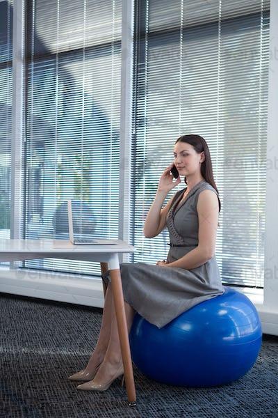 Female executive sitting on exercise ball while talking on mobile phone