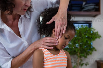 Mid-section of physiotherapist giving neck massage to girl patient