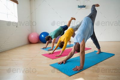 Instructor with students practicing downward facing dog pose with feet up