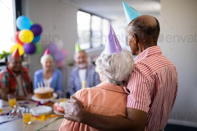 Rear view of senior couple looking at friends during party