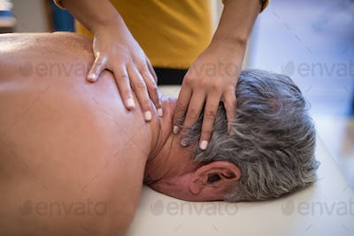 High angle view of female therapist giving neck massage to male patient