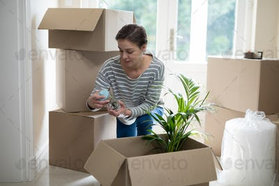 Woman opening cardboard boxes in living room