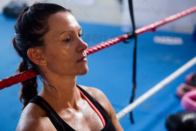Thoughtful female boxer leaning on rope
