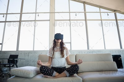 Businesswoman mediating while using virtual reality simulator in office