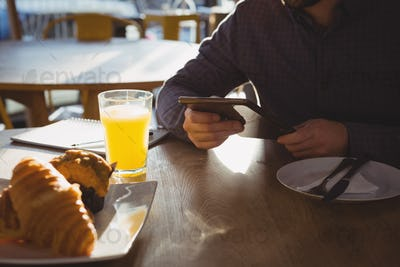 Mid section of businessman with breakfast using tablet in cafe