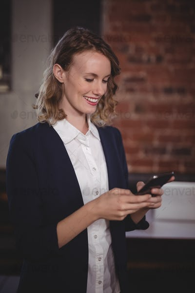 Smiling young beautiful female editor using smartphone at coffee shop