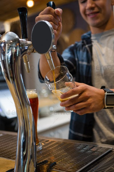 Bartender pouring drink from tap in glass at bar