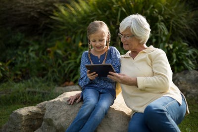 Smiling granddaughter and grandmother using digital tablet in garden