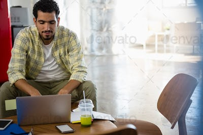 Young man using laptop at office