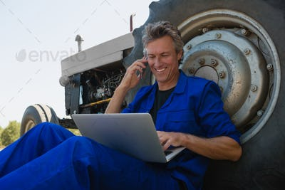 Worker talking on mobile phone while using laptop