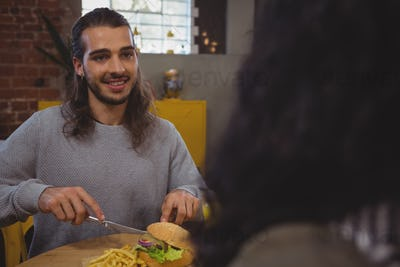 Man with friend having burger in cafe