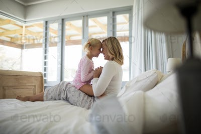 Mother and daughter having fun in the bedroom