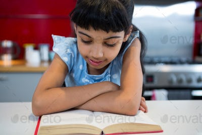 Girl with arms crossed reading novel at home