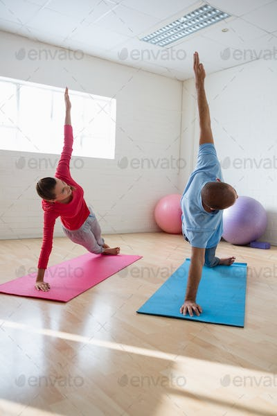 Yoga instructor with student practicing side plank pose in club