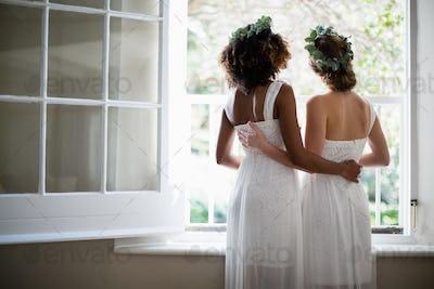 Rear view of women standing near window