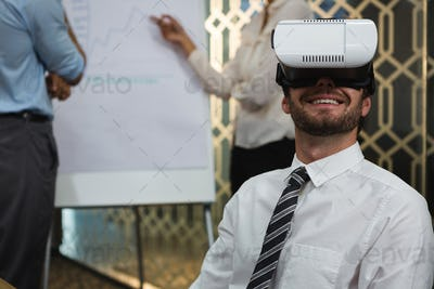 Businessman using virtual reality headset in conference room