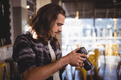 Side view of young male photographer holding DSLR camera