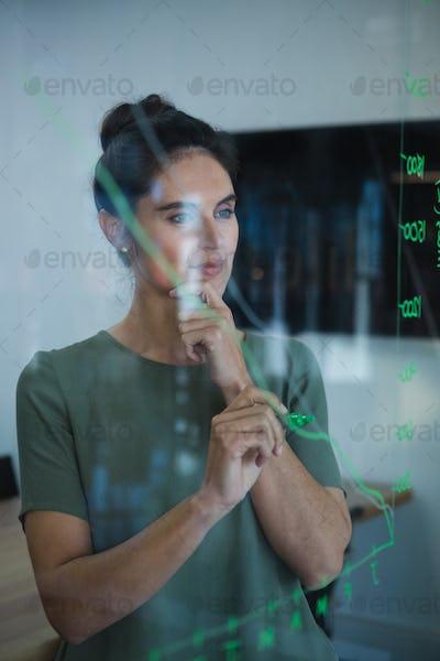 Female executive writing on glass