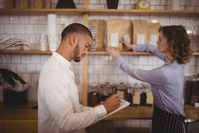 Young male owner writing on clipboard while waitress arranging products