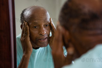 Concerned senior man reflecting on mirror