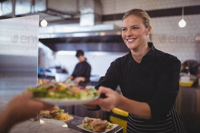 Attractive young female chef giving fresh Greek salad to waiter