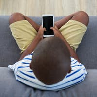 Overhead view of boy using mobile phone on sofa