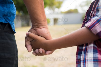 Cropped image of boy and grandfather holding hands