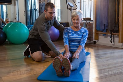 Physiotherapist assisting senior woman in exercise