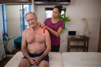 Female therapist applying elastic therapeutic tape on shoulder of frowning shirtless senior male pat