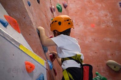 Determined boy practicing rock climbing