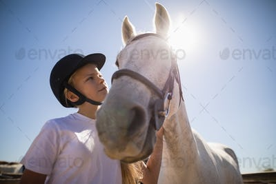 Rider girl looking at the white horse