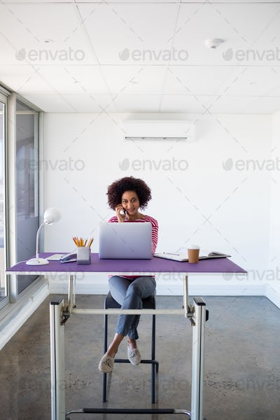 Female executive talking on mobile phone while working over laptop
