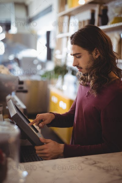 Side view of young waiter with long hair using cash register at counter