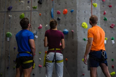 Rear view of trainer with athletes standing by climbing wall