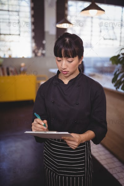 Young attractive female chef writing on clipboard while standing at cafeteria