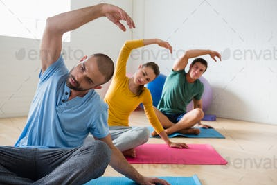 Yoga instructor with students exercising at club