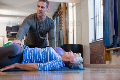 Physiotherapist assisting senior woman in performing exercise on mat