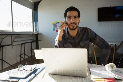 Man talking on phone while sitting at desk in office